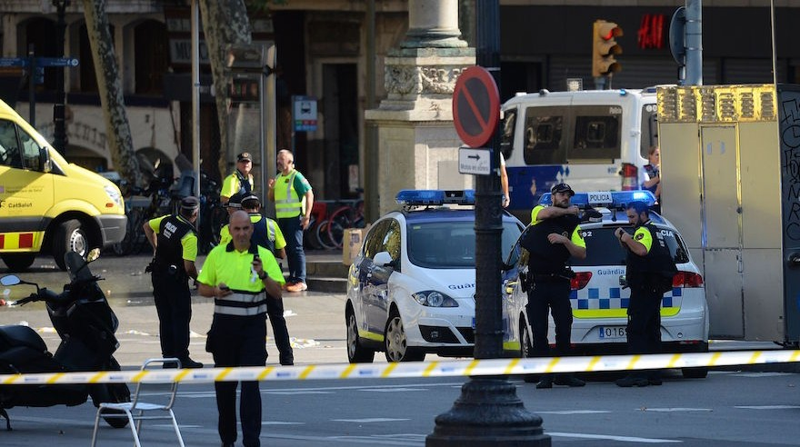 Medical staff members and policemen standing in a cordoned-off area after a van ploughed into the crowd on the Las Ramblas Boulevard in Barcelona Spain